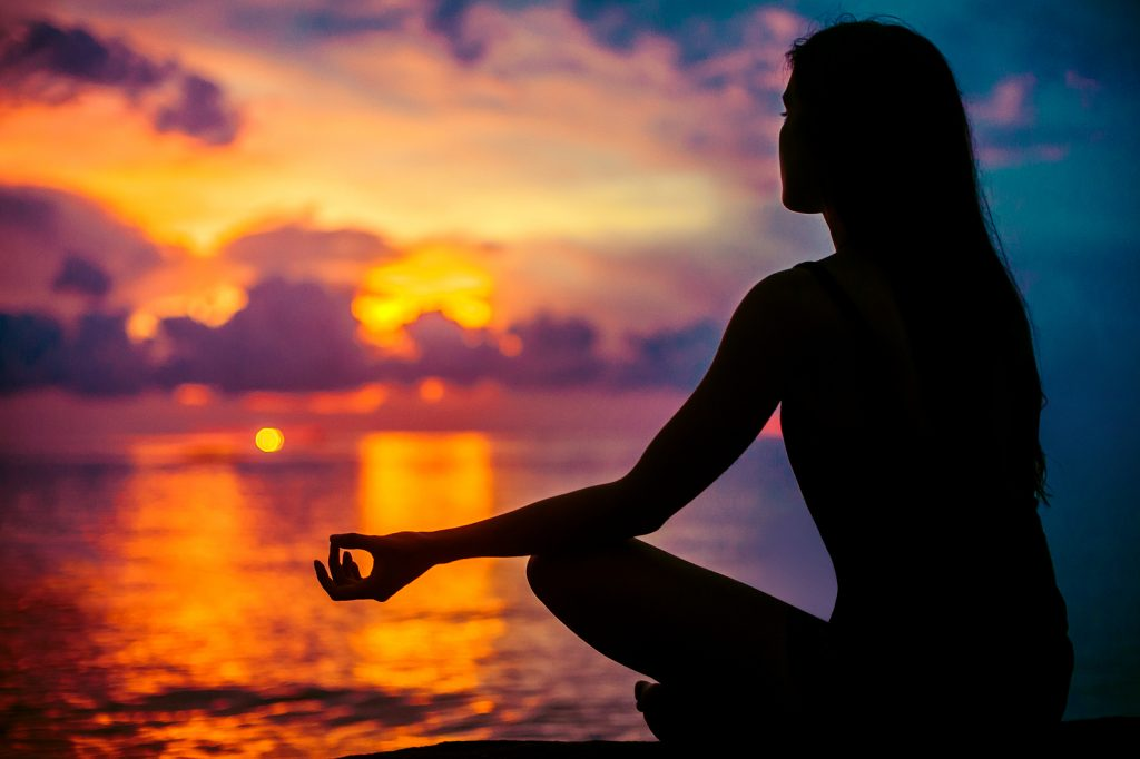 woman meditating at sunset by a body of water | Anxiety treatment | Anxiety therapist | Counseling in Washington DC 20036