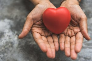 hands holding a rubber pink heart representing having compassion for yourself. This skill is taught during eating disorder treatment for anorexia in Washington DC 20036at Monarch Wellness and Psychotherapy