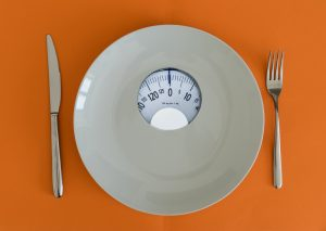 White plate with weight scale illustrating an eating disorder concept for binge eating disorder and compulsive overeating. Begin eating disorder treatment in Washington DC 20036