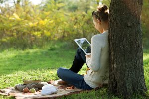 woman looks at her tablet during an online therapy session for anxiety and anorexia in Virginia in the park. She gets help from Monarch Wellness and Psychotherapy who also provides online therapy in Maryland and online therapy in Washington DC