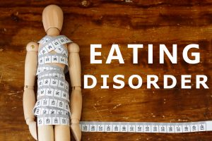 wooden doll covered in measuring tape next to the words eating disorder. This illustrates the need for online eating disorder therapy in Washington DC for compulsive eating, anorexia, bulimia, and binge eating disorder with Monarch Psychotherapy and Wellness 20036