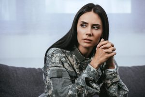 female woman in an army uniform looks sad while experiencing symptoms of trauma. She gets trauma treatment and online trauma therapy in washington DC with monarch psychotherapy and wellness 20036
