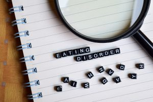 letters on a notebook spelling eating disorder next to a magnifying glass. Monarch wellness and psychotherapy offers online therapy for eating disorders in Washington DC, Virginia, and Maryland