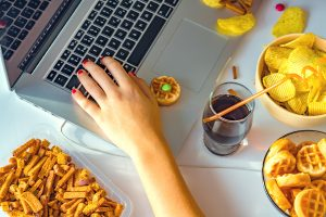 person working at their computer next to junk food. They get online eating disorder treatment in Washington DC for emotional eating with Monarch Wellness and Psychotherapy