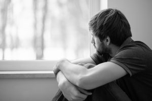 young man stairs out the window after experiencing trauma. He receives trauma therapy and online trauma therapy in washington DC with monarch psychotherapy and wellness 20036